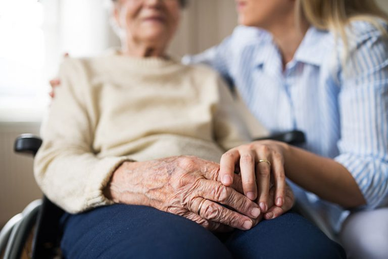 adult woman holding hands of senior woman in wheelchair